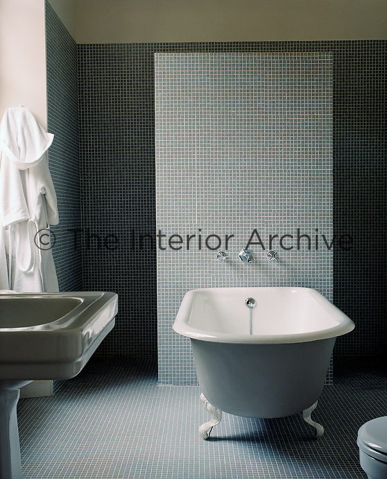 The bathroom is completely tiled in grey mosaic and a shower is concealed behind a partition separating it from the free-standing bath