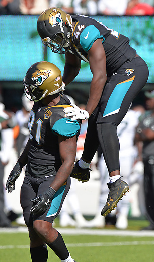 Jacksonville Jaguars linebacker Myles Jack (44) jumps on defensive end Yannick Ngakoue (91) after Ngakoue's sack with 35 seconds to play in the second quarter against the New York Jets in a NFL game Sunday, October 1, 2017 in East Rutherford, NJ. (Rick Wilson/Jacksonville Jaguars)