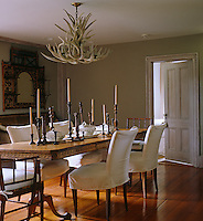 A pine table with a Greek key motif, French chairs upholstered in white loose covers and an antler chandelier make an interesting dining room