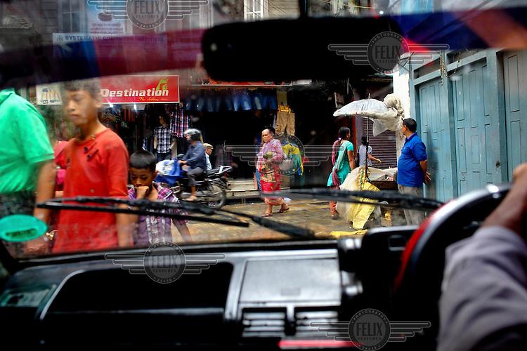 A driver goes along a busy street in Kathmandu.