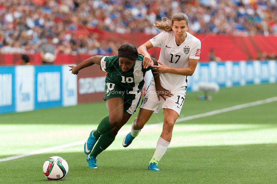 June 16, 2015: Courtney DIKE of Nigeria and Tobin HEATH of the USA fight for the ball during a Group D match at the FIFA Women's World Cup Canada 2015 between Nigeria and the USA at BC Place Stadium on 16 June 2015 in Vancouver, Canada. USA won 1-0. Sydney Low/Asteriskimages.com