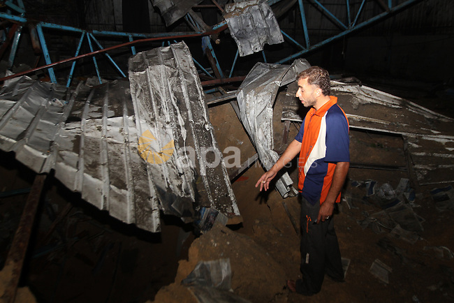 A Palestinian man inspects debris in a destroyed car wash garage after Israeli airstrike in the Al Tuffah area in the east of Gaza City, in the Gaza Strip on 12 July 2011.. Photo by Ali Jadallh