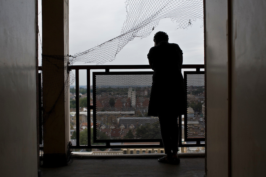 Vicky Laker, a resident of Alexandra Court Homeless Hostel on Stoke Newington High Street, looks through a broken pigeon net on the ninth floor of the building.