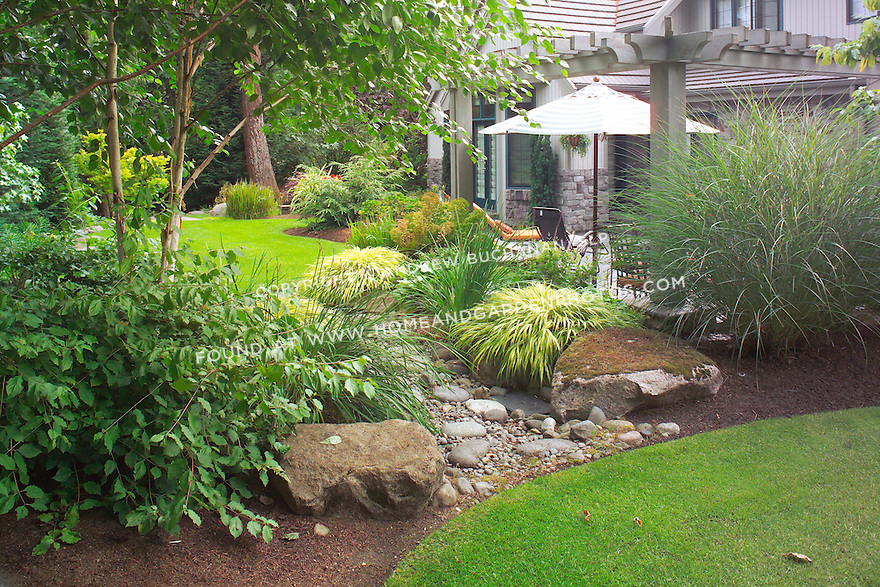 The upper, contemplative area of this small suburban backyard east of Seattle is a Zen-like design of small lawns designed as ponds, with large and small rocks as dry strembeds that connect them. Design by Sander Groves landscapes, Inc.