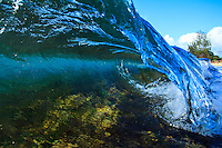 A close-up of a small colorful wave breaking over a shallow reef on the North Shore of O'ahu.