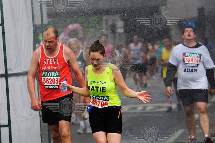 Charity runners near the tail of the pack in the London Marathon going through a water tunnel to try and cool down.
