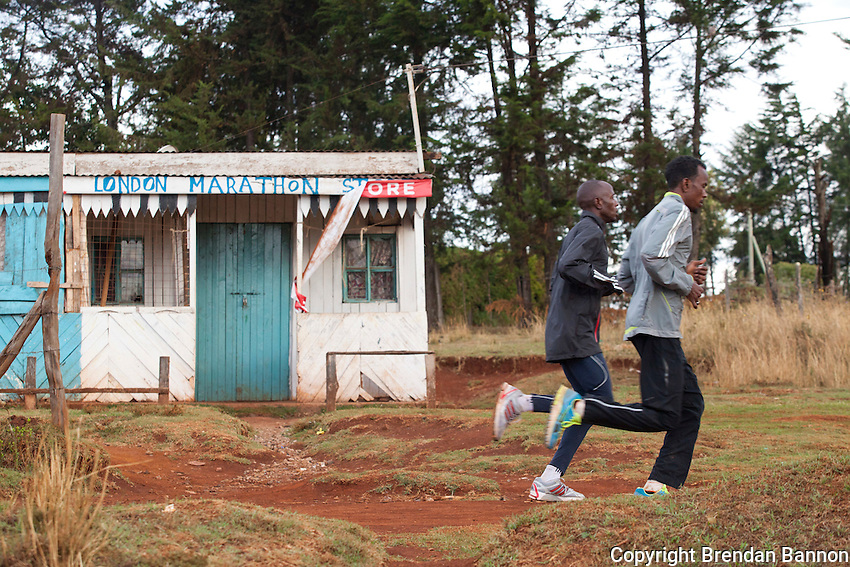 """Athletes in Iten Kenya run past the """"London Marathon Store."""" Kenya's elite and amatuer runners mingle on the high altitude roads and trails of this small town."""