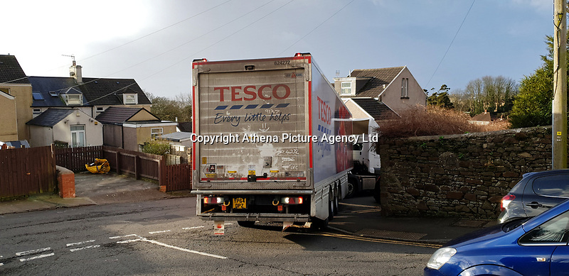 Pictured: The Tesco lorry remains stuck for the second time at the bottom of Rose Hill in Swansea, Wales, UK.  Tuesday 11 February 2020<br /> Re: A Tesco articulated lorry remained stranded in a narrow residential street for hours in the early hours of the morning, only to get stuck again moments after the its driver managed to get moving again. The lorry attempted to negotiate turning from Terrace Road into Rose Hill in the Mount Pleasant area of Swansea after apparently its driver was following his sat nav. The driver of a white car-which was parked legally- was traced and moved his car just after 9am. A few hundred metres the lorry got stuck again trying to negotiate a tight right hand turn, due to cars parked -legally- on either side of the road.