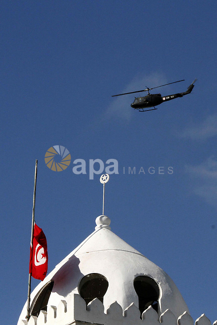 A military helicopter is seen as Tunisians take part a demonstration to demand a new government free of officials of the ousted regime of former president Zine el Abidine Ben Ali, goes on in central Tunis, Tunisia, 23 January 2011. According to media reports, hundreds of people from throughout Tunisia started arriving on 23 January in the capital Tunis, as part of what was called a caravan of liberation . Tunisia marked its final day of a three-day mourning period for those killed in the weeks-long massive street protests on 23 January. Photo by Karam Nasser