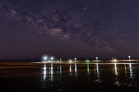 This is composite of the Caldwell Pier in Port A Texas and the milky way taken on the same beach and put together to create what you could see the futher away you were from the lights of the pier.  The stars were really nice, so we cruise down the beach to a spot with less light and captured the sky for this image.  You have the pier at night with the light and the stars over head to make for a perfect image.    Port A Texas had just recently had severe damage to this sleepy beach town from  just over 3400 people prior to Hurricane Harvey which did heavy damage to the area and it will be years before this area comes back fully. We are with you and hope you come back soon as we look forward to visiting again soon.