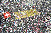 Switzerland. Canton of Neuchâtel. Neuchâtel. Grape Harvest Festival. A swiss flag and colorful confetti on the concrete road during the flower parade (corso).  © 2006 Didier Ruef