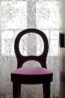 A rose-pink velvet covered chair in the study in front of antique lace curtains covering the French windows