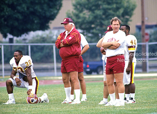 Washington Redskins head coach Richie Petitbon, center, and offensive coordinator Rod Dowhower, right, look on as their team warms-up during Washington Redskins training camp at Dickinson College in Carlisle, Pennsylvania on July 26, 1993.  Redskins running back-kick returner Brian Mitchell (30) looks on from left.<br /> Credit: Ron Sachs / CNP