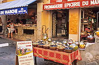 France, Provence. St. Tropez. Stall selling olives and fresh fish shop in background.