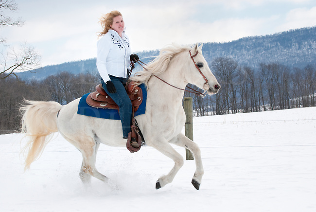 Picture of pretty blonde woman riding her white Arabian horse through a field at the edge of a snowy woods.