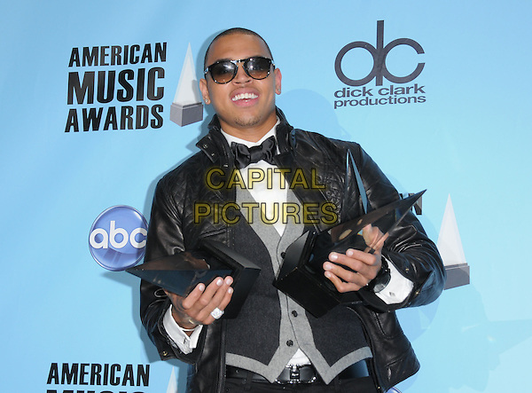 CHRIS BROWN.The 2008 American Music Awards held at Nokia Theatre Live L.A. in Los Angeles, California, USA..November 23rd, 2008      .AMA AMAs pressroom half length black leather jacket waistcoat sunglasses shades trophy trophies award grey gray .CAP/DVS.©Debbie VanStory/Capital Pictures.