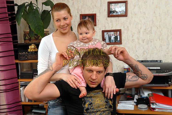 Fedor Emelianenko with spouse Marina and daughter Vasilisoj.House photosession.April 27th, 2008.half length black t-shirt tattoos pink carrying kid child father dad family married husband wife white mother mom mum on shoulders .CAP/PER/VB.©VB/PersonaStars/CapitalPictures