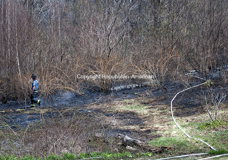 TORRINGTON, CT, 04 MAY 15 - A Torrington firefighter walks through brush that burned behind 473 Weed Road in Torrington Monday afternoon.    Alec Johnson/ Republican-American