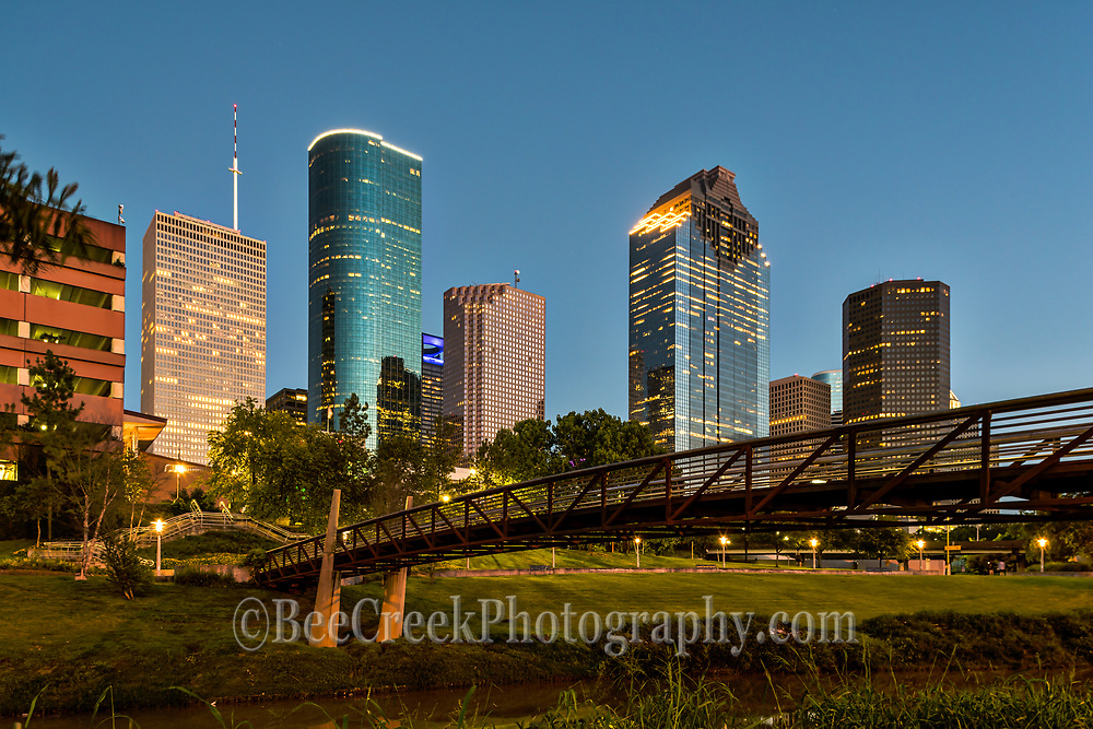The Sabine promenade pedestrian bridge in downtown area with Houston skyline at blue hour. Twilight is one of our favorite times to photograph skylines in Houston and this was a great capture as the lights on the high rise building came on just after the sun went down and you could still see the blue in the sky on this evening in the city.  Houston is a city of high rise skyscrapers with some of the tallest in Texas and the southern US. The JP Morgan Chase comes in at whopping 1002 feet and the Well Fargo  building in this image comes as the second tallest building in the city at 992 feet  while the Heritage Plaza to the right comes in at 762 ft still a very impressive of the city skycrapers.
