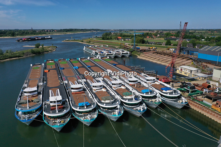 Foto: VidiPhoto<br /> <br /> ARNHEM/DODEWAARD - Cruiseschepen en rondvaartboten liggen al anderhalve maand werkloos aan de Rijnkade in Arnhem en in de Waalhaven bij Dodewaard (foto). Vanwege de coronamaatregelen mogen er voorlopig geen passagiers aan boord en varen de schepen niet. In Arnhem liggen vooral cruiseschepen van Nederlandse maatschappijen. Bij de gemeente Arnhem hebben zij inmiddels een verzoek ingediend om geen liggeld te hoeven betalen. De haven van Dodewaard is voorlopig de ankerplaats voor de vloot toeristenschepen die normaal op de Europese rivieren vaart. Een deel van de schepen is eigendom van Scylla AG, een rederij uit Zwitserland die op verschillende Europese rivieren vaart. De totaal 32 schepen van de vloot liggen allemaal stil in verschillende havens. De schepen zelf hebben net hun grote winter-onderhoudsbeurten gehad.