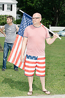 A man wearing American flag shorts and carrying an American flag watches the 4th of July Parade in Amherst, New Hampshire, on Thu., July 4, 2019.