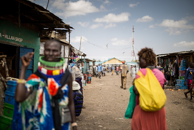 A woman in a  street scene in   Kakuma, Kenya.Kakuma refugee camp in North of Kenya. Kakuma is the site of a UNHCR refugee camp, established in 1991. The population of Kakuma town was 60,000 in 2014, having grown from around 8,000 in 1990. In 1991, the camp was established to host the 12,000 unaccompanied minors who had fled the war in Sudan and came walking from camps in Ethiopia.