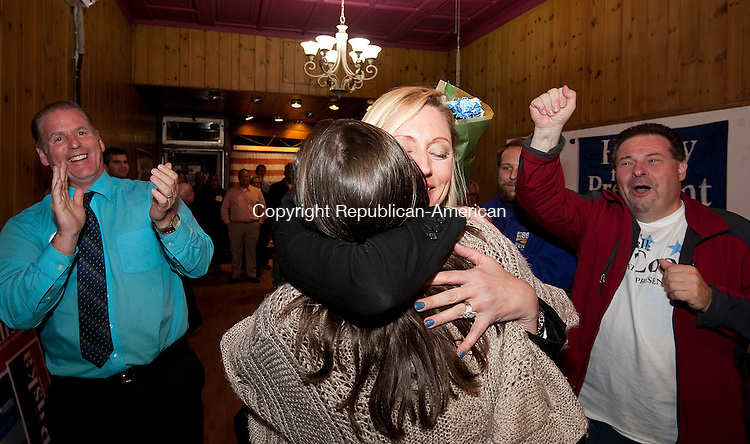 TORRINGTON,  CT-110816JS25- Michelle Cook (R-Torrington) is congratulated by  her daughter Ashlynn Cook after winning her 65th House District race against Republican challenger Todd Schaller Tuesday at Democratic Campaign Headquarters on Main Street in Torrington. Looking on is Michelle's husband Chris Cook, left. Ashlynn, who is attending college in Maryland,  made a surprise trip home. <br />  Jim Shannon Republican American