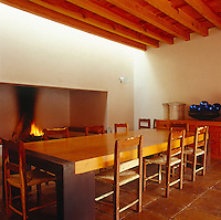 The dining room is dominated by a large open fireplace and a long wooden table