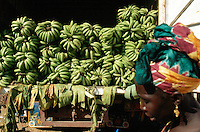 Gambia. Serrekunda. Serrekunda is 20 km away from Banjul, the capital of the republic of  Gambia.  A woman dressed with a headscarf passes-by a truck fully loaded with fresh bananas on market day. © 2000 Didier Ruef