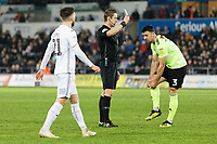 Referee John Brooks (C) shows a yellow card to Enda Stevens of Sheffield United during the Sky Bet Championship match between Swansea City and Sheffield United at the Liberty Stadium, Swansea, Wales, UK. Saturday 19 January 2019