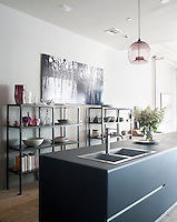 A glass pendant light hangs above the kitchen island fitted with a sink by Smeg and the photograph is by Eric Slayton