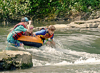Janelle Jessen/Herald-Leader<br /> Jasper Franco (from left), Sophie Denison and Sterling Maples went down the rapids in the Siloam Springs Kayak Park while spending a day at the river last week.