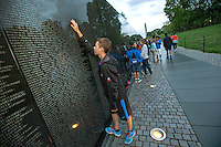 A teenage student reads the names on the Vietnam Memorial in Washington DC.