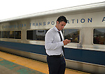 Merrick, New York, U.S. - July 14, 2014 - During evening rush hour, a young man in business shirt and tie leaves the train and looks at his smart phone as he walks on elevated platform of Merrick train station of Babylon branch, after MTA Metropolitan Transit Authority and Long Island Rail Road union talks deadlock, with potential LIRR strike looming just days ahead.
