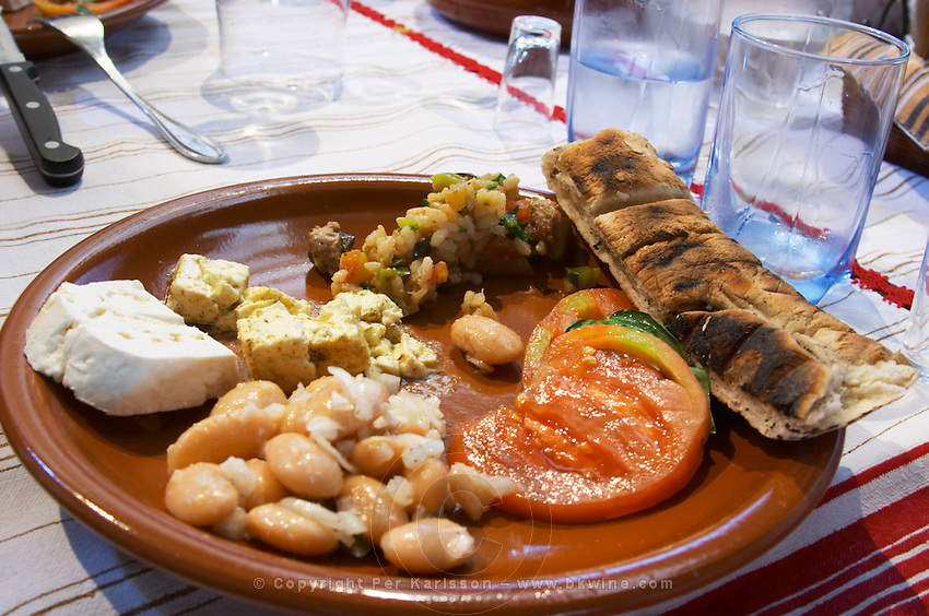 An earthenware plate with tomato and basil leaf salad, vegetable risotto, white beans and onion salad and traditional bread. Pita type bread called kulaç kulac. White beans typical for south east Albania. Goat cheese from northern Albania Tradita traditional restaurant, Shkodra. Albania, Balkan, Europe.