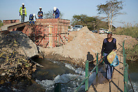 MUFULIRA, ZAMBIA- JULY 6: Glencore contractors construct a small bridge that collapsed and stranded people between villages and Mufilira on July 6, 2016. Glencore, an Anglo-Swiss multinational commodity trading and mining company, owns about 73 % of Mopani mines, which produces copper and some cobalt. The mine employs about 15,000 people. (Photo by Per-Anders Pettersson)