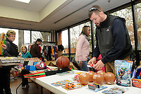 STAFF PHOTO FLIP PUTTHOFF <br /> SHEEP DOG CHRISTMAS GIFTS<br /> Clay Dodson, right, arranges Christmas gifts for children on Saturday during the Sheep Dog Impact Assistance Christmas program on Saturday Dec. 20 2014 at the Center for Nonprofits in Rogers. Members of Sheep Dog Imact Assistance helps families of military, law enforcement and fire service members who need assistance during the holidays and through the year, said Shain Scott with Sheep Dog. The event featured lunch, craft making and Christmas gifts for children.