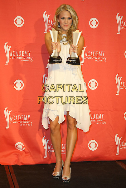 CARRIE UNDERWOOD.Pressroom at the 44th Annual Academy Of Country Music Awards held at the MGM Grand Garden Arena, Las Vegas, Nevada, USA..April 5th, 2009.full length white cream dress award trophy trophies gold peep toe shoes layers layered .CAP/ADM/MJT.© MJT/AdMedia/Capital Pictures.