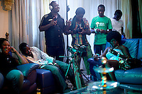 """Actors ( Betsy Ikeme holding her phone on the right ) and crew take a small brake while shooting  a long scene on the set of a 21 episodes Nollywood Soap production called """"Close Shave""""  in Lagos, Nigeria on Sunday August 9 2009...Currently Nigerian films outsell Hollywood films in Nigeria and many other African countries. Nollywood is a nascent film industry in Nigeria, growing within the last two decades to become the third largest film industry on the planet, behind the United States and Indian film industries. Nigeria has a US$250 million movie industry, churning out some 200 movies for the home video market every month."""