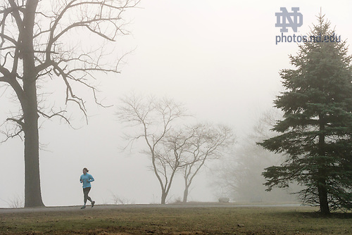 February 22, 2017; A students jogs around St. Mary's Lake in the early morning fog.  (Photo by Barbara Johnston/University of Notre Dame)