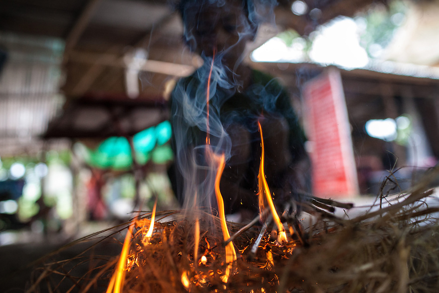 un, the son of Mr Newachiti Kamla, holds bamboo sticks over a fire to make them more flexible. 06/08/2013 © Thomas Cristofoletti / Ruom