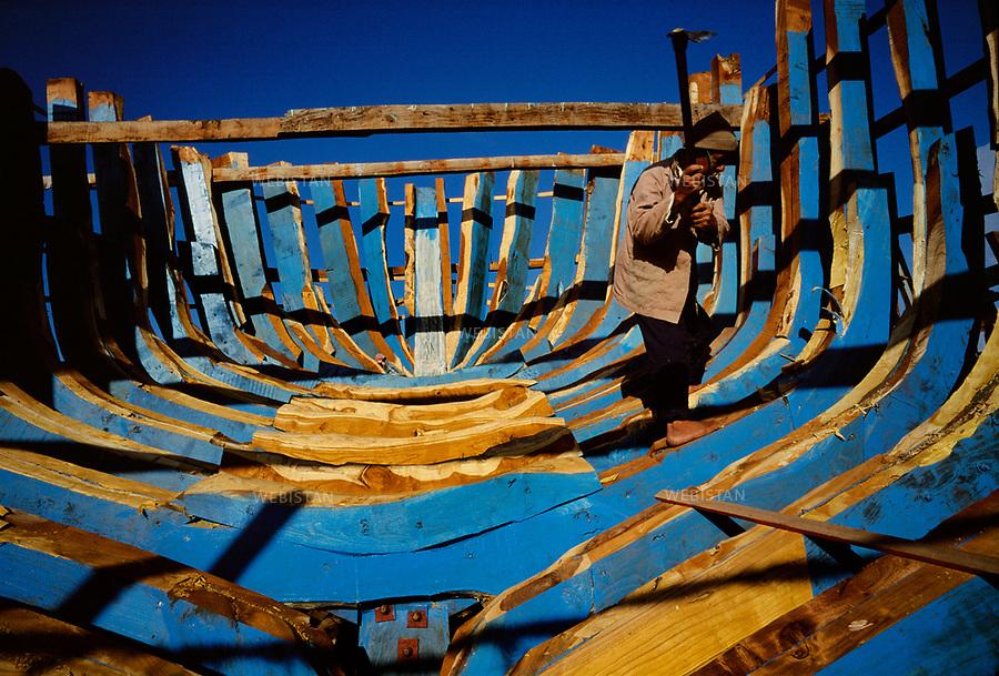 Egypt, Dumyat, 1996Construction of a fishing boat in the city of Dumyat, with a millennial tradition for fishing and woodworking. This artisan uses the same three tools used for his craft at the time of the Pharoahs. This photo was shot during a reportage on the Nile Delta for National Geographic Magazine.<br /> Egypte, Dumyat, 1996 <br /> Construction traditionnelle d&rsquo;un bateau de p&ecirc;cheurs dans la ville de Dumyat, cit&eacute; &eacute;gyptienne historique des p&ecirc;cheurs et des menuisiers. Ce travailleur utilise seulement trois outils pour fa&ccedil;onner un bateau en bois, les m&ecirc;mes qui furent construits du temps des Pharaons. Image r&eacute;alis&eacute;e dans le cadre d'un reportage sur le delta du Nil pour le National Geographic Magazine.