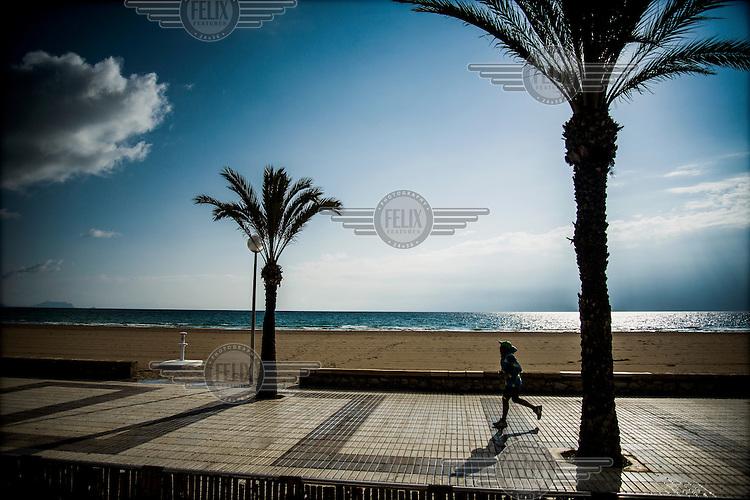 A person jogging along the sea front at Playa Muchavista.