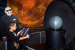 Oakland CA Parent chaperone and 2nd grade boy study touch screen and model explaining planets at Chabot Space and Science Center