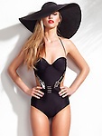 Beautiful young woman wearing a one-piece monokini swimsuit and a black wide brim sun hat isolated on white wall background