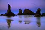 Jagged rocks and ocean surf waves on coastal beach at dawn, Bandon State Beach, Bandon, Oregon