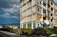 "A Cuban woman walks in front of the large apartment block in Abel Santamaría, a public housing suburb of Santiago de Cuba, Cuba, 31 July 2008. The Cuban economic transformation (after the revolution in 1959) has changed the housing status in Cuba from a consumer commodity into a social right. In 1970s, to overcome the serious housing shortage, the Cuban state took over the Soviet Union concept of social housing. Using prefabricated panel factories, donated to Cuba by Soviets, huge public housing complexes have risen in the outskirts of Cuban towns. Although these mass housing settlements provided habitation to many families, they often lack infrastructure, culture, shops, services and well-maintained public spaces. Many local residents have no feeling of belonging and inspite of living on a tropical island, they claim to be ""living in Siberia""."