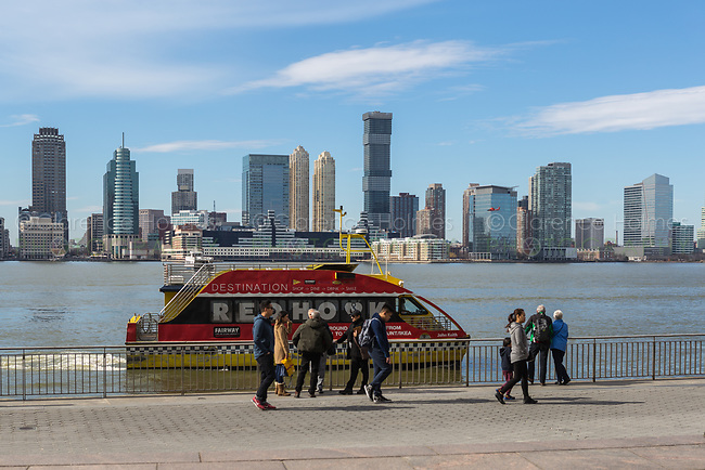 A NY Waterway ferry arrives at the World Financial Center Ferry Terminal, with the skyline of Jersey City in the background across the Hudson River.