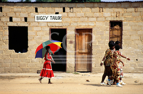 "Victoria Falls, Zambia. ""Biggy Tailors"", girl in red dress with multicoloured umberella."