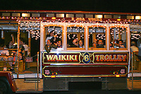Adorned with Christmas lights, the Waikiki Trolley guides visitors thru downtown Honolulu to see the giant Christmas Tree in the Honolulu Hale courtyard.